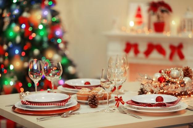 暖炉の背景に休日の装飾とクリスマステーブルの設定