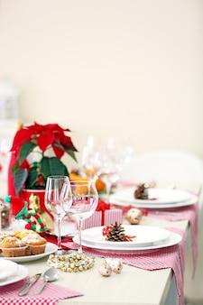 밝은 배경에 휴일 장식이 있는 크리스마스 테이블 설정