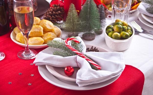 Сервировка рождественского стола с праздничными украшениями.