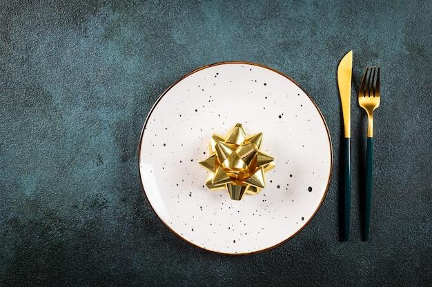 暗い背景にモダンな食器や装飾が施されたクリスマステーブルセッティング。上面図。新年の場所の設定。装飾が施されたクリスマス食器。クリスマスの場所の設定。