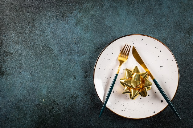 Christmas table setting with modern dishware and decorations on dark background. top view. new year place setting. christmas tableware with decorations. christmas place setting.