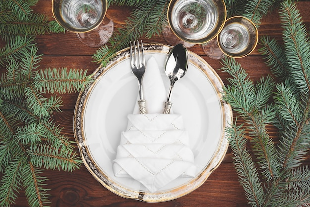 Christmas table setting with pine tree branches and decorations top view