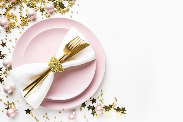 Christmas table setting with pink dishware, golden silverware on white . top view.