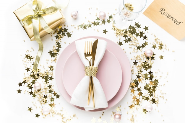 Christmas table setting with pink dishware, golden silverware on white