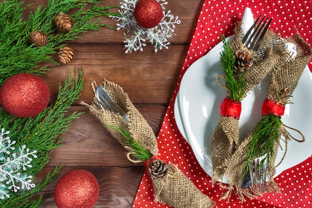 Christmas table setting with plate, silverware and decorations
