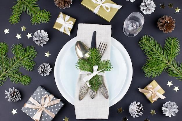 Сервировка рождественского стола с тарелками, столовым серебром, подарочной коробкой и украшениями в черном и золотом цветах. вид сверху