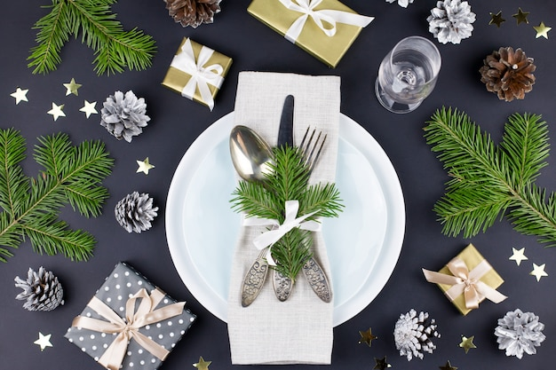 Christmas table setting with plates, silverware, gift box and decorations in black and gold colors. top view