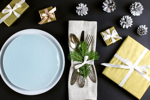 Christmas table setting with plates, silverware, gift box and decorations in black and gold colors