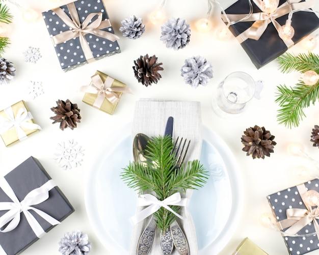 プレート、銀器、プレゼント、装飾品を備えたクリスマステーブルセッティング。上面図