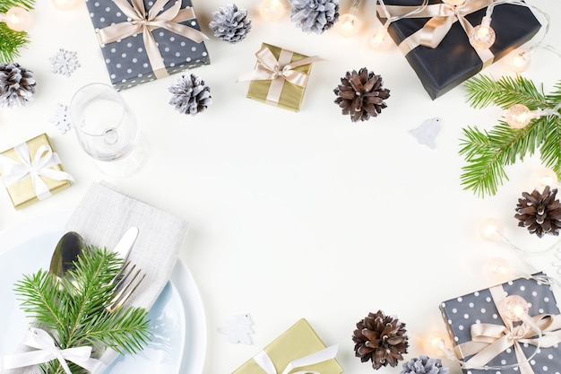 プレート、銀器、プレゼント、デコレーションを備えたクリスマステーブルセッティング。上面図