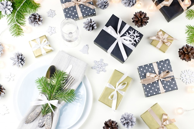 Christmas table setting with plates, silverware, presents and decorations . top view
