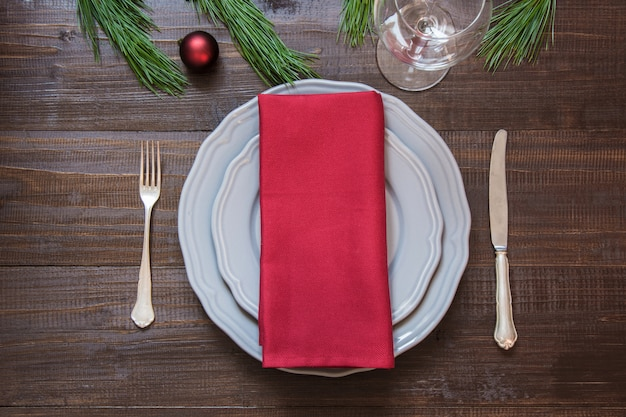 Christmas table setting with red ball, silverware and decorations on wooden board.