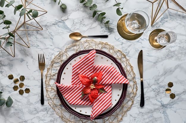 Christmas table setting with red napkin, golden utensils and fresh eucalyptus leaves on white marble background