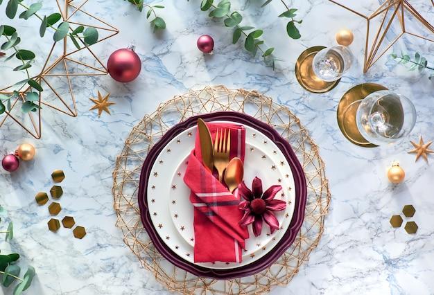大理石の背景に赤いナプキン、ポインセチア、金の道具、ユーカリとクリスマステーブルの設定を残します。フラットは、金色のカトラリー、エレガントなプレート、幾何学的な六角形のテーブルの上に置いた。