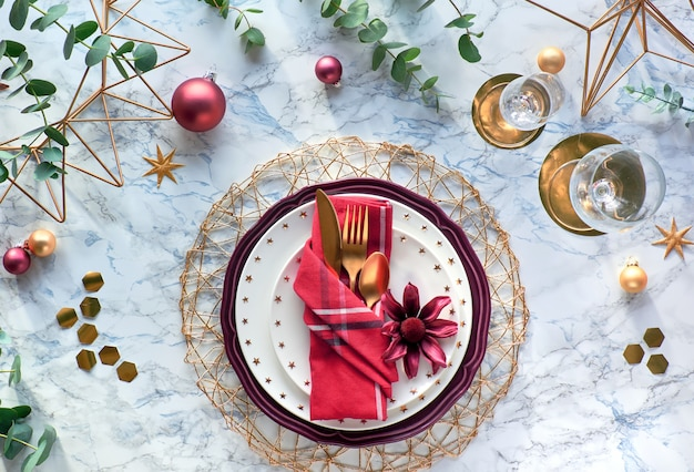 Christmas table setting with red napkin, poinsettia, gold utensils and eucalyptus leaves on marble background. flat lay on table with golden cutlery, elegant plates and geometric hexagons.