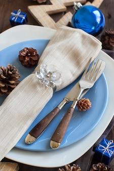木の素朴な装飾が施されたクリスマステーブルの設定をクローズアップ
