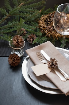 Christmas table setting with silverware and dark natural evergreen decor.