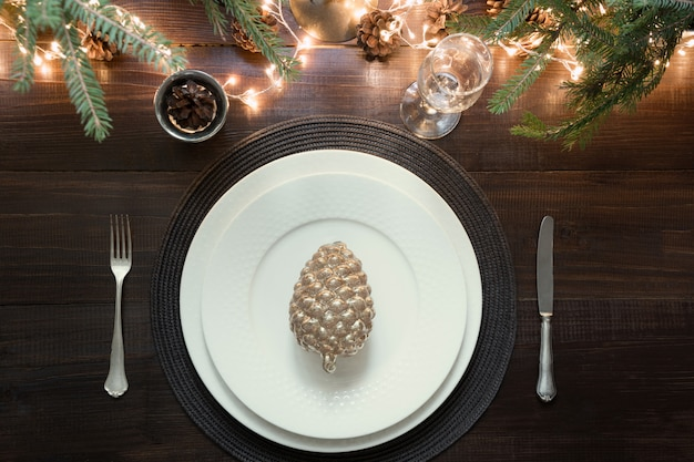 Christmas table setting with silverware, garland and dark decor.