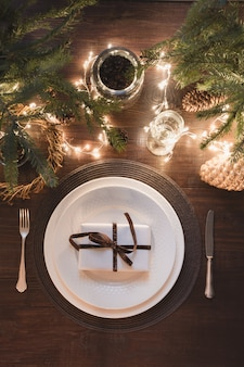 Christmas table setting with silverware, garland and evergreen decor.