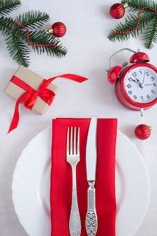 白いテーブルクロスに赤い目覚まし時計が付いたクリスマステーブルセッティング。上面図。閉じる。