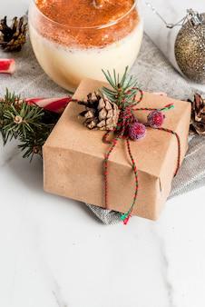 Рождественская сервировка на белом мраморном столе с традиционным зимним коктейлем eggnog, рождественским подарком, конфетой, сосновыми шишками и елочным шаром