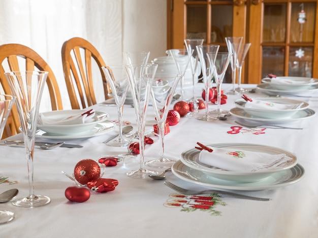 白い背景にヴィンテージ食器、銀器、赤い装飾が施されたクリスマステーブルの設定。選択的な焦点、クリスマスの概念