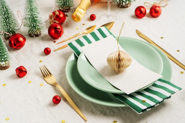 Christmas table setting with vintage tree toys, shiny confetti, golden cutlery on light linen tablecloth