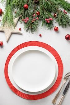 Сервировка рождественского стола с белыми и красными элегантными украшениями на белом столе. вид сверху. вертикальный формат.