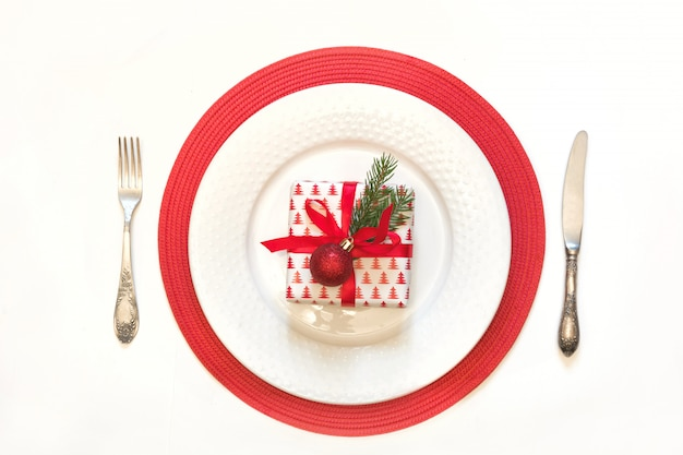 Christmas table setting with white dishware, silverware and red decorations on white.