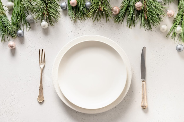 Christmas table setting with white holiday decorations.