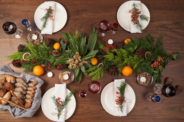 Сервировка рождественского стола с белыми пластинами и рождественской елкой на деревянном столе, вид сверху.