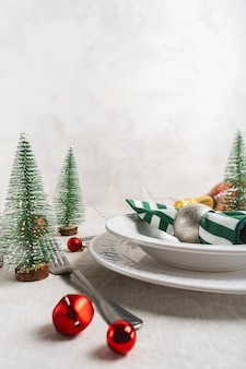 Christmas table setting with white plates, cutlery, napkin and with christmas decor on linen tablecloth with copy space. winter, festive concept table serving for new year.