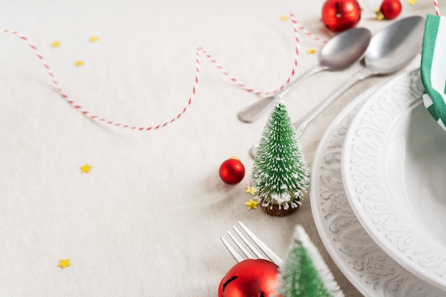 Christmas table setting with white plates, cutlery, napkin and with christmas decor