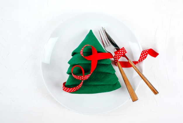 Christmas table setting with white plates and green christmas tree, top view napkin fold on white