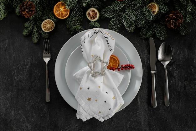 Сервировка новогоднего стола белыми тарелками серебряные столовые приборы с праздничной салфеткой на темном бетоне