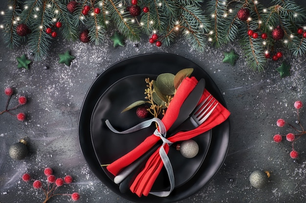 Christmas table setup on dark. flat lay with xmas decorations in green and red