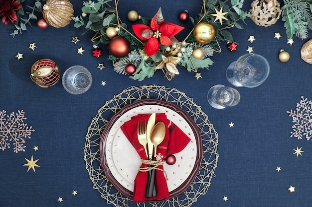 Christmas table setup with dark red white plates, red paper ring and poinsettia, golden utensils. red, green and golden gilded decorations. flat lay.