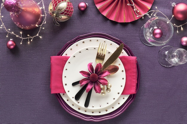 Сервировка новогоднего стола с золотым, розовым и красным декором на фиолетовой льняной ткани. тарелки с цветами, посудой и лозой.