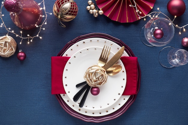 Christmas table setup with white plate, golden utensils, dark red and gilded decor. flat lay, top view on dark blue linen textile table. xmas lights garland.