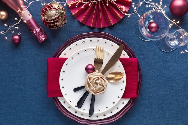 Christmas table setup with white plate, golden utensils, dark red napkin and gilded decorations. flat lay, top view on dark blue linen textile background. xmas lights garland.
