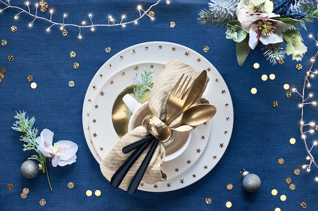 Christmas table setup with white plate and golden utensils and gilded decorations