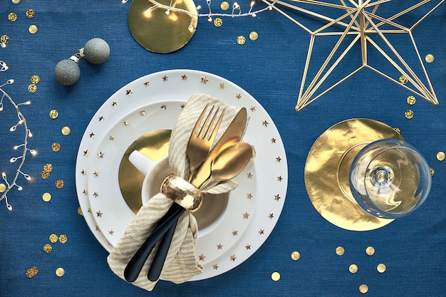 Christmas table setup with white plate and golden utensils and gilded decorations.