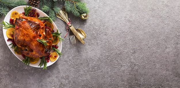 Christmas table with baked chicken is festively decorated with candles.