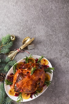 Christmas table with baked turkey or chicken, copy space for text.