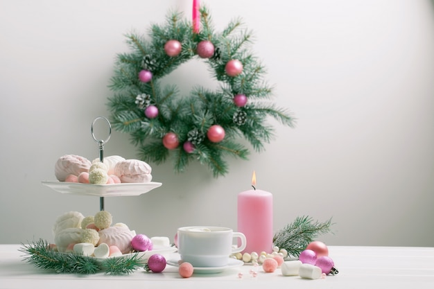 Christmas table with cup of coffee and dessert