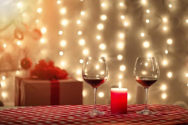 白のクリスマスツリーの近くのワインを2杯とクリスマステーブル