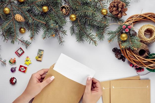 封筒に手紙を入れて女性の手が色々なアイテムのクリスマステーブル