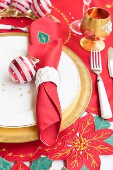 白と金色のプレート、ナイフ、フォークのクリスマステーブルをクローズアップ