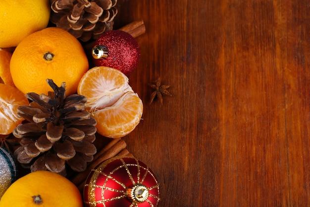 クリスマスのタンジェリンと木製のテーブルのクローズアップのクリスマスのおもちゃ