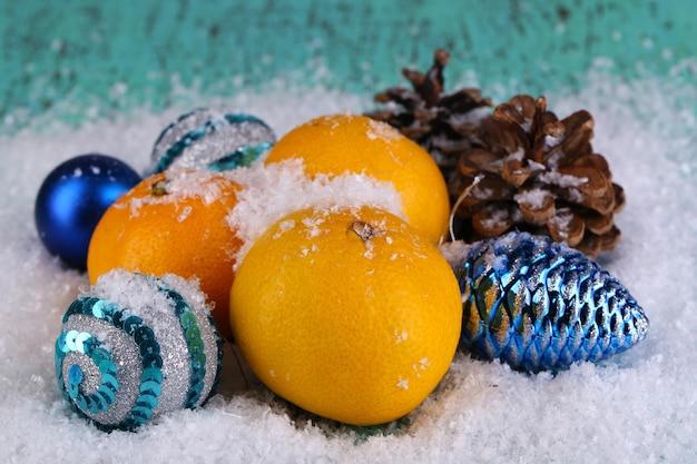 雪の上の木製のテーブルの上のクリスマスのみかんとクリスマスのおもちゃ